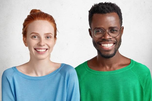 Cintura para arriba retrato de pareja de raza mixta con cálidas amplias sonrisas felices de pasar tiempo juntos.