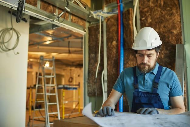 Cintura para arriba retrato de trabajador de la construcción barbudo con casco y mirando los planos de planta mientras se renueva la casa, espacio de copia