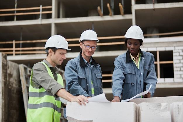 Cintura para arriba retrato de trabajadores discutiendo planos de planta en el sitio de construcción espacio de copia