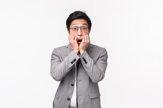 Cintura de emocionado entusiasta joven trabajador asiático en traje, escuchando con interés chismes, historias interesantes, tomados de la mano cerca de la boca y mirando sin palabras en la pared blanca