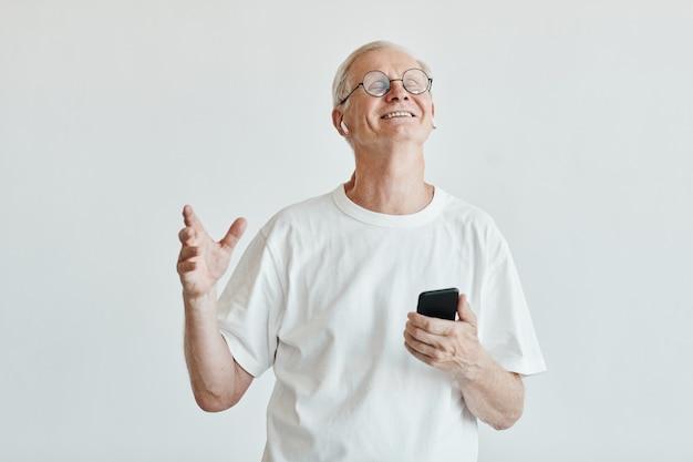 Cintura mínima para arriba retrato del hombre mayor sonriente bailando y sosteniendo el teléfono inteligente contra el fondo blanco.