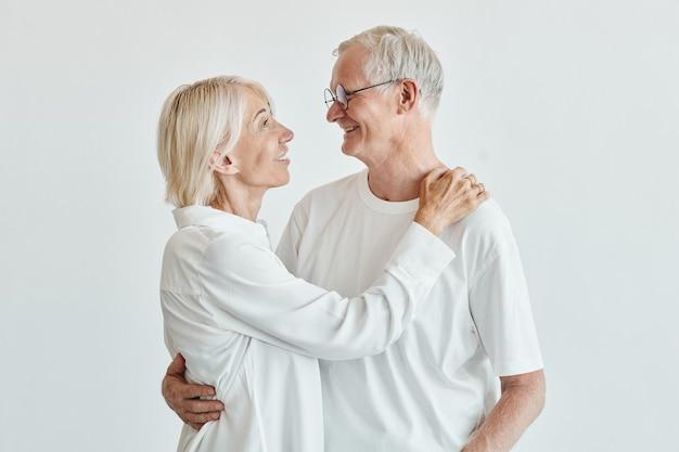Cintura mínima para arriba retrato de la moderna pareja senior abrazándose contra el fondo blanco y mirando ...