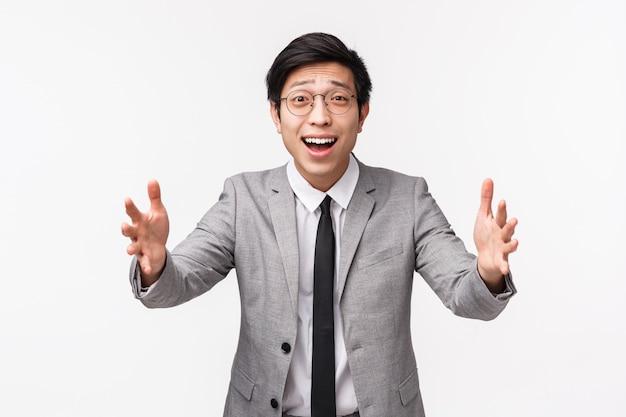Cintura del tonto y lindo gerente de oficina asiático masculino, ven a casa y extiende las manos para abrazar a su hermanita, sonríe, mira con amor y cuidado, usa un traje gris en la pared blanca