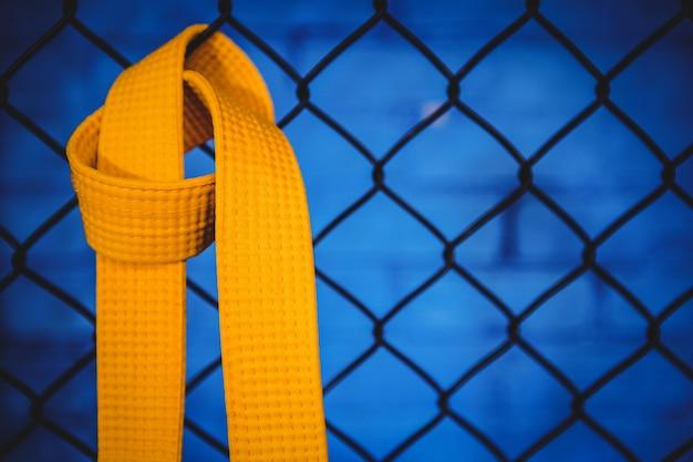 Cinturón amarillo de karate colgado en la cerca de malla de alambre
