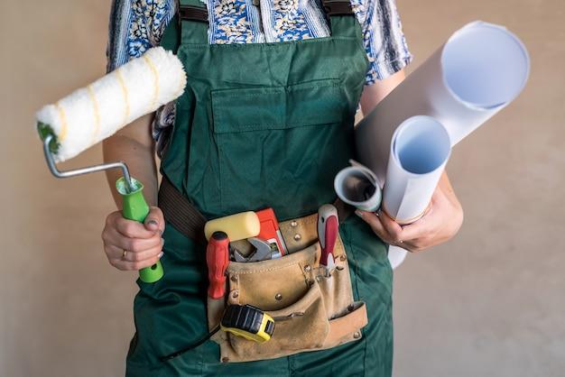 Cinturón de constructor con herramientas y manos con planos