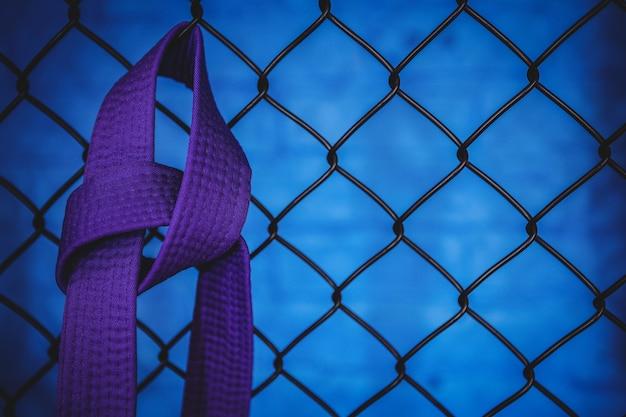 Cinturón morado de karate colgado en una cerca de malla