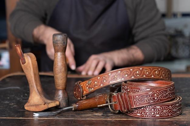 Cinturones de cuero con herramientas de cuero en mesa y artesano trabajando detrás.