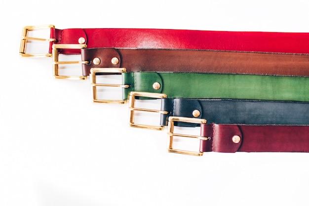 Cinturones multicolores. muchos cinturones de cuero en un blanco. los cinturones rojos, amarillos, azules, marrones y verdes están tallados en un blanco
