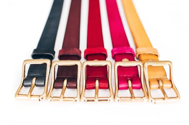 Cinturones multicolores. muchos cinturones de cuero sobre un fondo blanco. los cinturones rojos, amarillos, azules, marrones y verdes están tallados en un blanco
