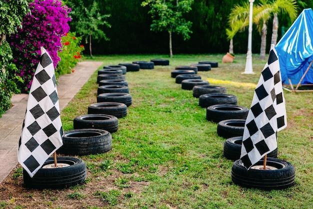 Circuito de carreras con neumáticos en un patiotrasero para que los niños jueguen en carreras, con una bandera a cuadros.