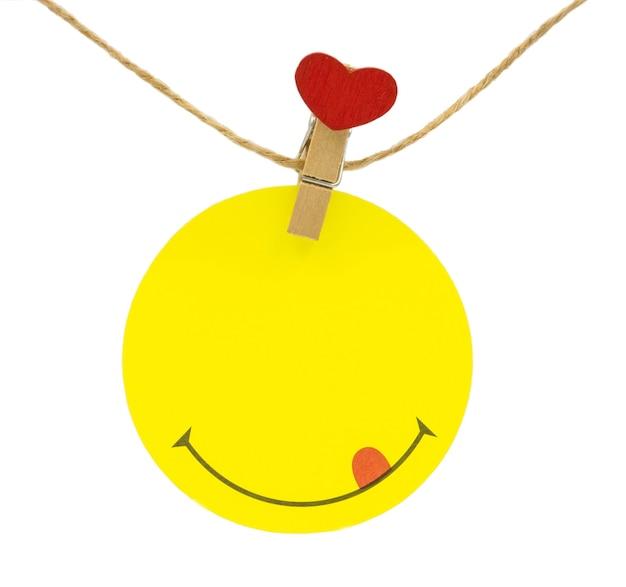 Círculo amarillo nota de san valentín colgando del cable con clips con cabeza de corazón rojo aislado en blanco