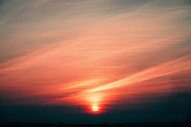 El círculo anaranjado del sol se eleva detrás del horizonte rosado en las nubes de fondo de tonos cálidos.