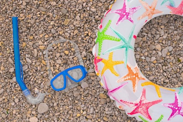 Círculo de bebé inflable sandalias máscara de buceo con tubo, tumbada en la playa.