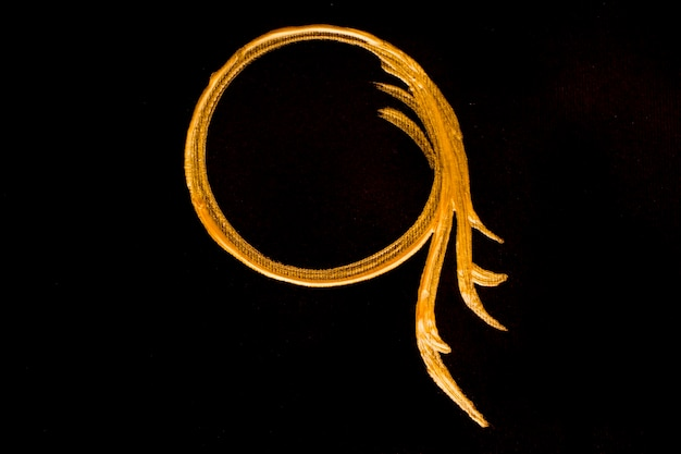 Círculo dorado pintado sobre fondo negro