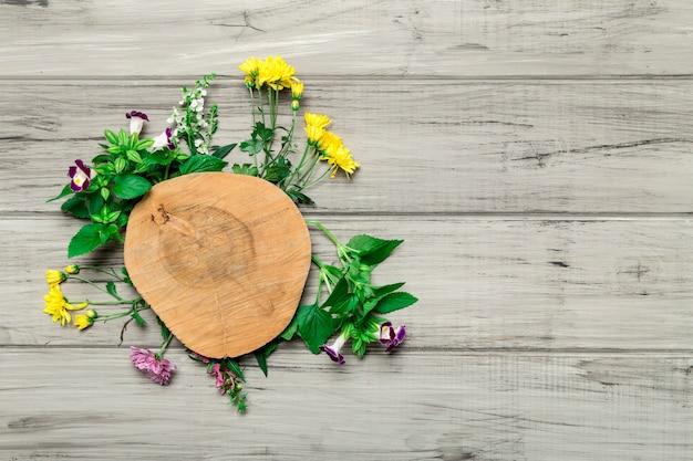 Círculo de madera con flores brillantes alrededor.