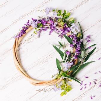 Círculo de madera con flores y hojas.