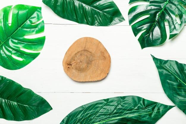 Círculo de madera y hojas verdes alrededor.