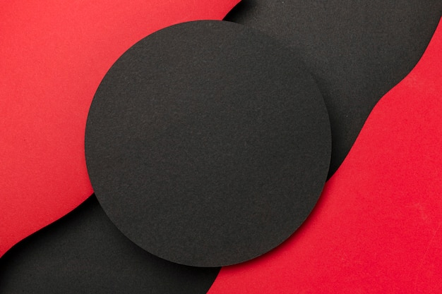 Círculo negro y capas onduladas de fondo rojo.