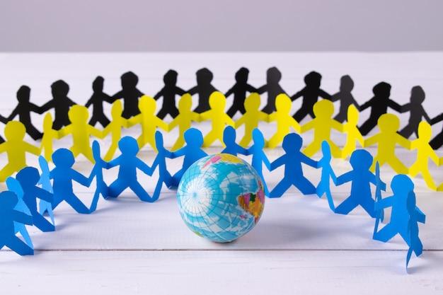 Círculo de personas de papel tomados de la mano alrededor del globo hecho de papel cortado