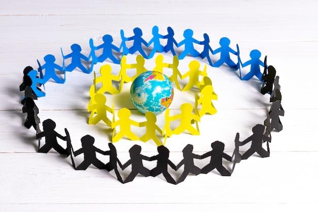 Círculo de personas de papel tomados de la mano alrededor del mundo hecho de papel cortado