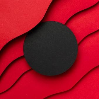 Círculo vacío negro y capas onduladas de fondo rojo.