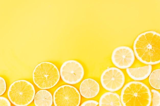 Círculos de frutas cítricas sobre fondo amarillo