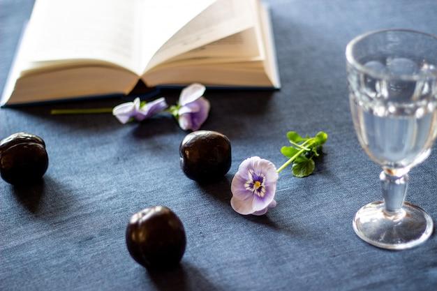Ciruelas, flores, un libro y un vaso de agua sobre un fondo azul.