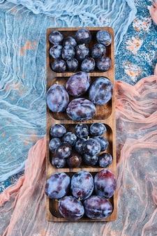 Ciruelas de jardín en bandeja de madera y en azul con manteles.