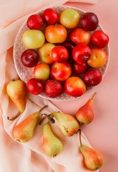 Ciruelas maduras en un plato con peras