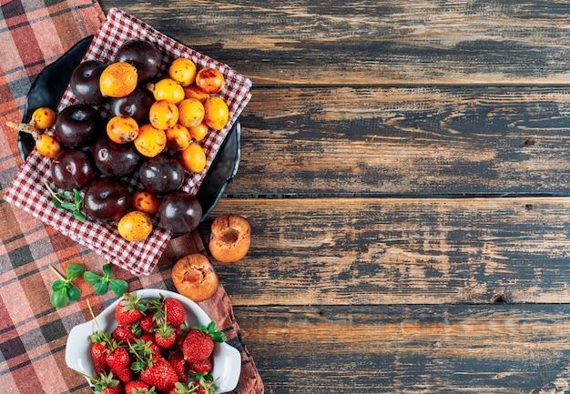 Las ciruelas, los nísperos y las fresas en un plato y una toalla de té con hojas verdes planas yacían sobre un fondo de madera oscura y tela de picnic.