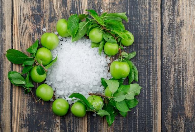 Ciruelas verdes con cristales de sal, hojas en la pared de madera, vista superior.
