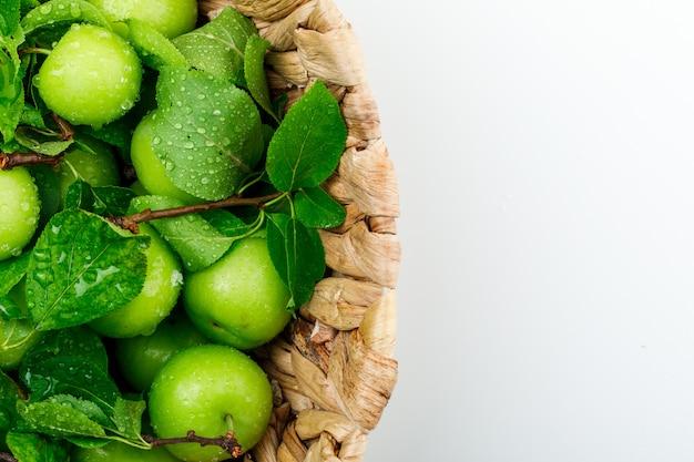 Ciruelas verdes lluviosas en una cesta de mimbre con hojas de primer plano sobre una pared blanca