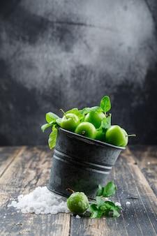 Ciruelas verdes en un mini cubo con cristales de sal, deja una vista lateral en la pared de madera y brumosa