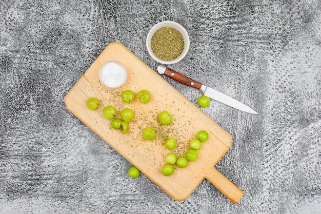 Ciruelas verdes picantes en una tabla de cortar con una pequeña barra de sal, tomillo seco y un cuchillo de frutas vista superior sobre una superficie gris grunge
