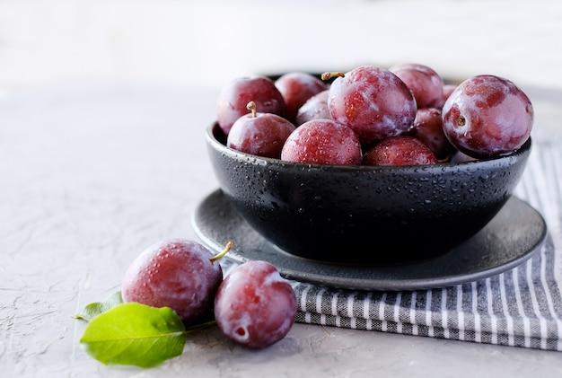 Ciruelas violetas frescas en el fondo de la mesa gris oscuro