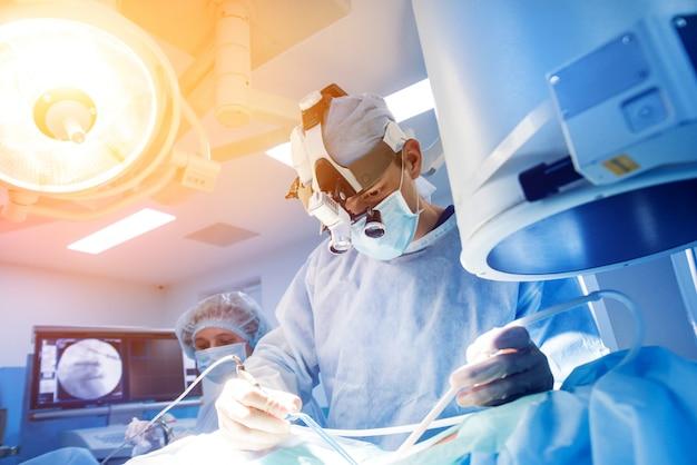 Cirugía de la columna. grupo de cirujanos en quirófano con equipo quirúrgico.