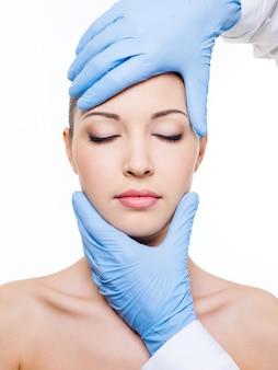 Cirugía plástica tocando la cabeza de un hermoso rostro femenino con los ojos cerrados