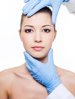 Cirugía plástica tocando el rostro de mujer hermosa. aislado en blanco