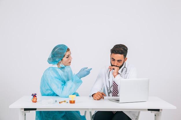 Cirujana y doctor discutiendo en la oficina