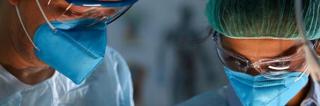 Cirujano y anastasiólogo en uniforme miran hacia abajo