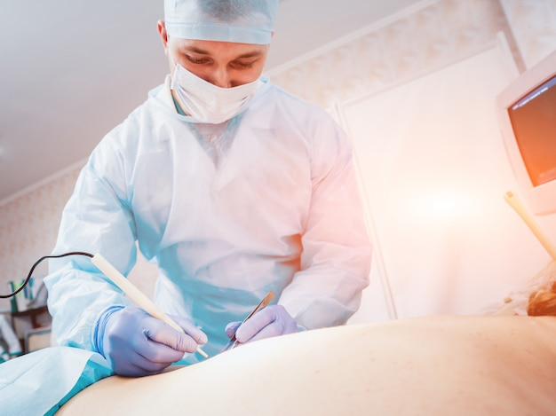 Cirujano y asistente en quirófano con equipo quirúrgico.