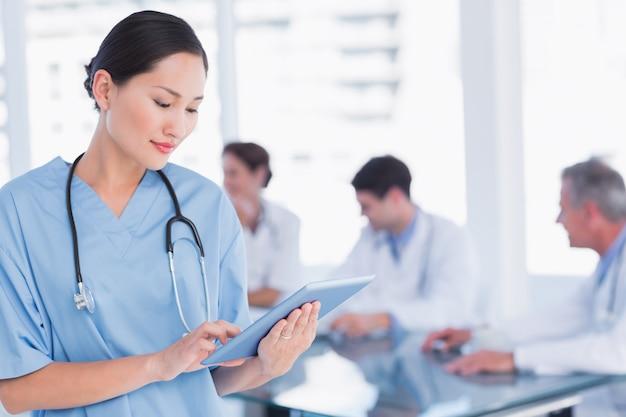 Cirujano con tableta digital con grupo alrededor de la mesa en el hospital