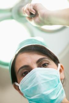 Cirujano de mujer sosteniendo una iluminación quirúrgica