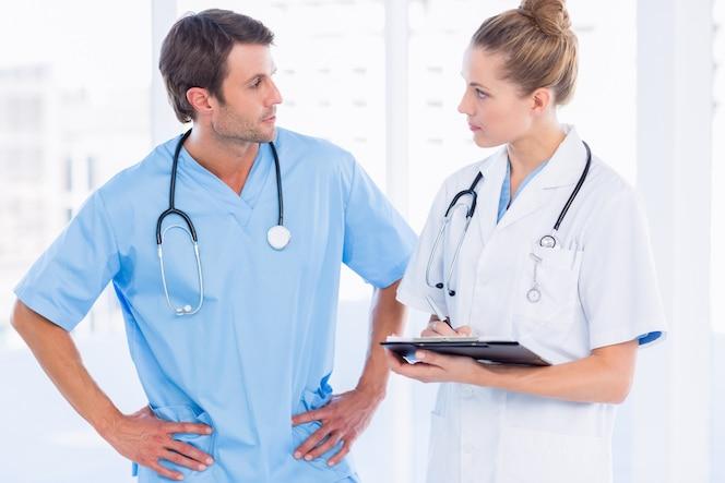 Cirujano de sexo masculino y doctora con informes médicos