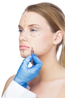 Cirujano dibujando líneas de puntos en la cara de los pacientes.