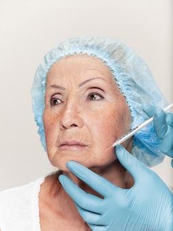 Cirujano haciendo un control de la piel de una mujer de mediana edad antes de la cirugía plástica