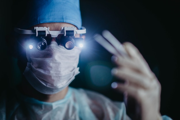 Cirujano con lupas binoculares opera a un paciente en un quirófano oscuro