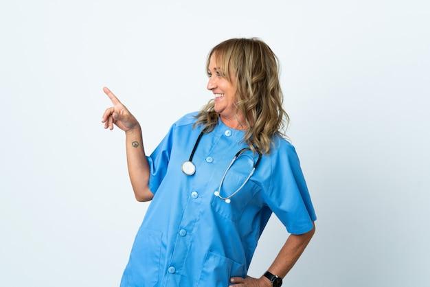 Cirujano de mediana edad mujer sobre antecedentes aislados apuntando con el dedo hacia el lado y presentando un producto