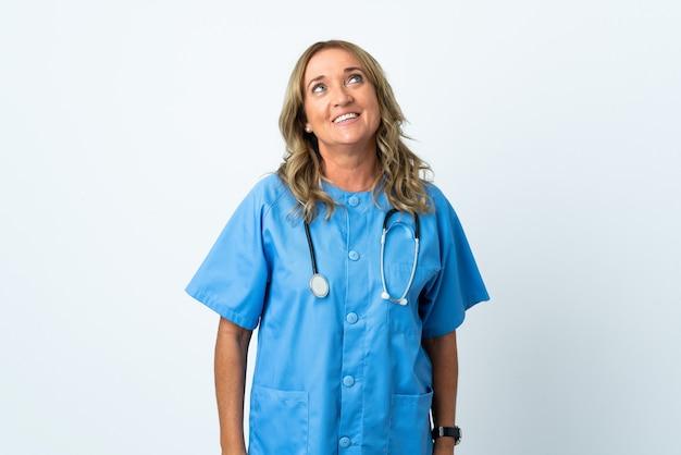 Cirujano de mediana edad mujer sobre antecedentes aislados pensando en una idea mientras mira hacia arriba