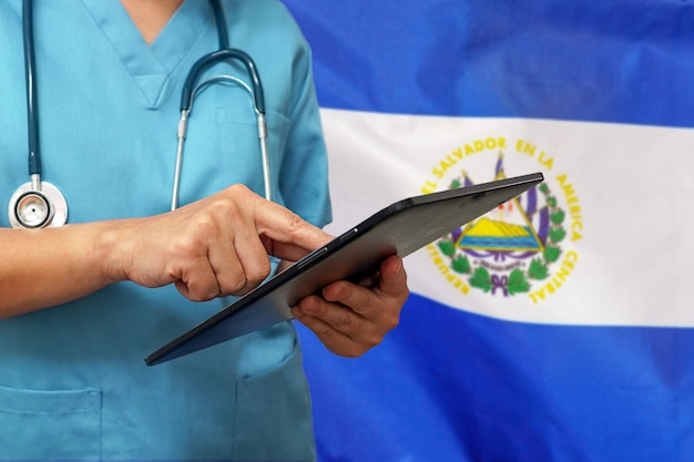 Cirujano o médico usando una tableta digital en el fondo de la bandera de el salvador